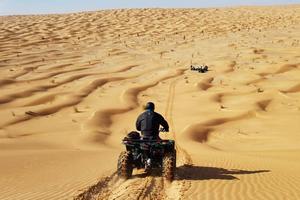 Un homme sur un quad descend une dune