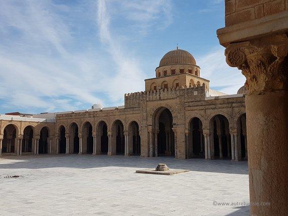 Au fond d'une grande cour avec un puits, un portique à arcades d'une mosquée